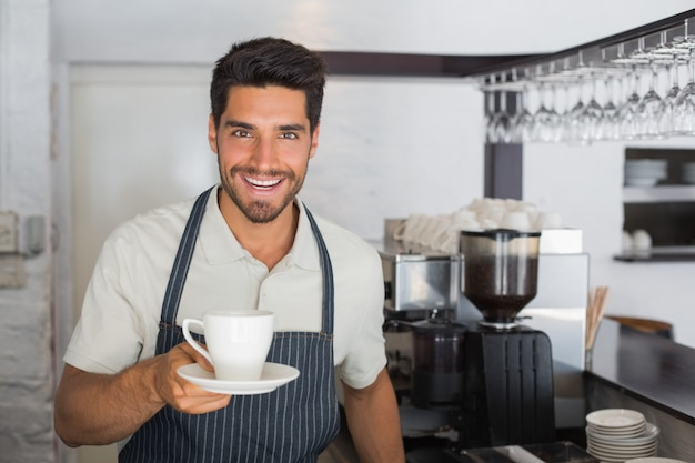 Smiling male barista holding cup of coffee at cafã©