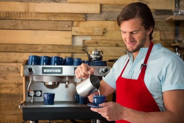 コーヒーショップでカップにミルクを注ぐ男性のバリスタの笑顔