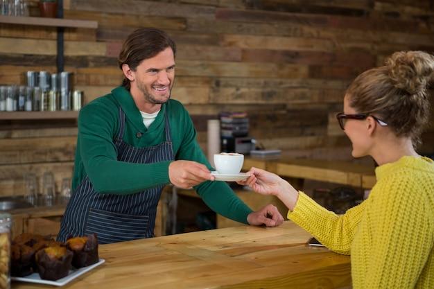カフェで女性のお客様にコーヒーを提供する笑顔の男性バリスタ