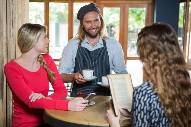 Улыбающийся мужчина-бариста, подающий кофе женщинам-клиентам в кафе