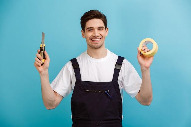 Улыбающийся мужчина-строитель держит резак и скотч на синей стене