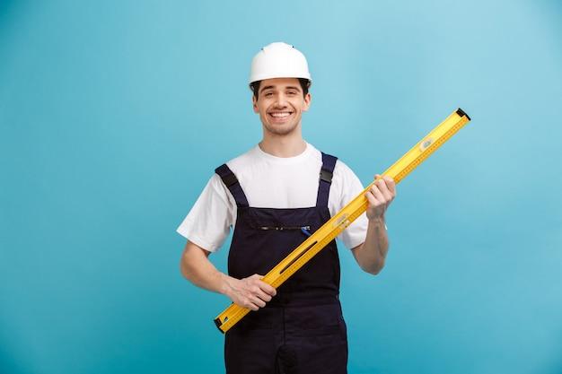 Улыбающийся мужчина-строитель в защитном шлеме, держащий инструмент уровня над синей стеной
