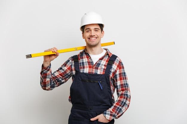 灰色の壁にレベルツールを保持している保護用のヘルメットで男性ビルダーを笑顔