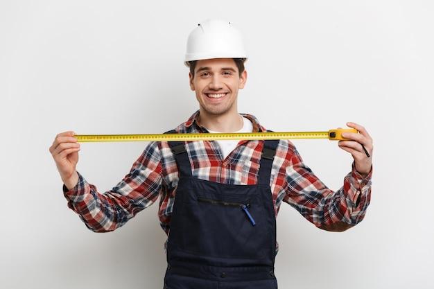 Улыбающийся мужчина-строитель в защитном шлеме показывает рулетку над серой стеной