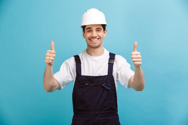 Улыбающийся мужчина-строитель в защитном шлеме показывает палец вверх над синей стеной