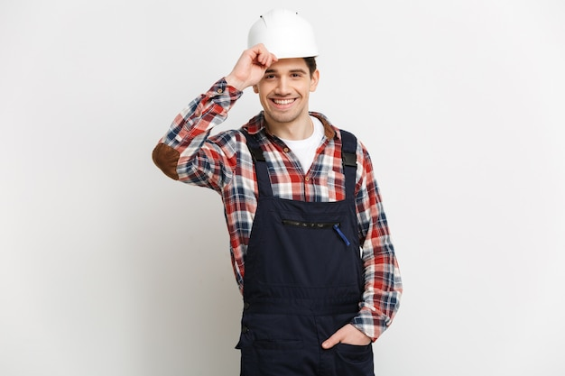 Улыбающийся мужчина-строитель в защитном шлеме позирует с рукой в кармане над серой стеной