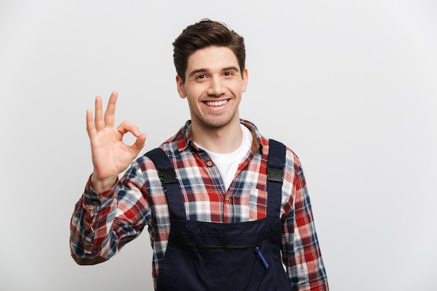 Smiling male builder showing ok sign  over grey wall