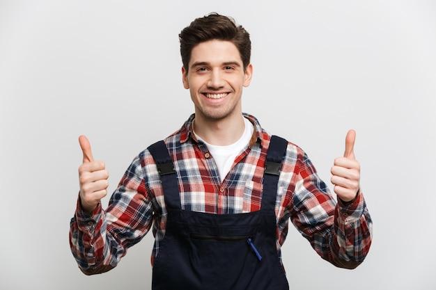 Улыбающийся мужчина-строитель показывает палец вверх над серой стеной