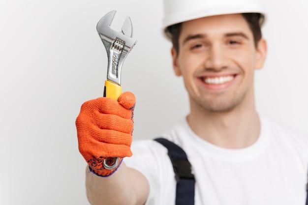 Улыбающийся мужчина-строитель, показаны гаечный ключ над серой стеной. сосредоточьтесь на гаечный ключ