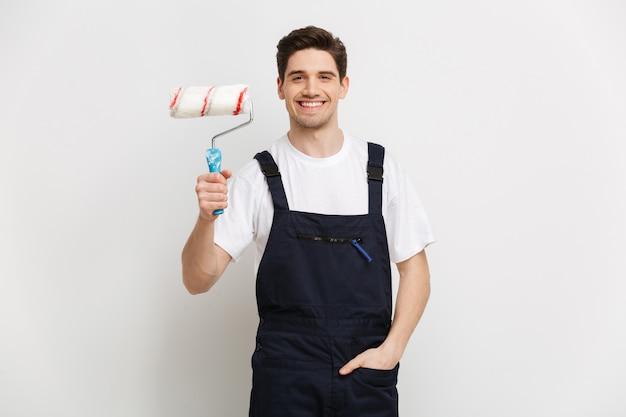 Улыбающийся мужчина-строитель с рукой в кармане, держащий рулон краски над серой стеной