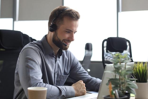現代のオフィスに座っているヘッドフォン、ノートパソコンの画面を見ているビデオ通話で笑顔の男性のビジネスコンサルタント。オンラインチャットを話している男性カスタマーサービスサポートエージェントヘルプライン。