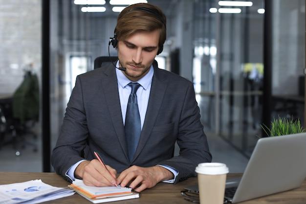 Улыбающийся мужской бизнес-консультант с наушниками, сидя в современном офисе, видеозвонок, глядя на экран ноутбука. человек горячей линии службы поддержки клиентов разговаривает в онлайн-чате.