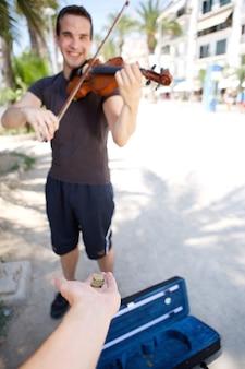 Улыбается мужской busker играть на скрипке