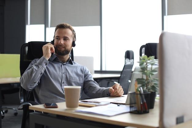 Улыбающийся мужчина-оператор call-центра с наушниками сидит в современном офисе, просматривает онлайн-информацию в ноутбуке, ищет информацию в файле, чтобы помочь клиенту.