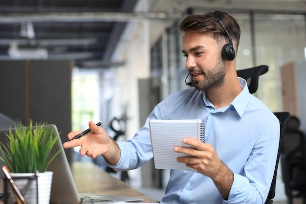 헤드폰을 끼고 웃고 있는 남성 콜센터 교환원은 현대적인 사무실에 앉아 노트북으로 온라인 정보를 상담하고 클라이언트를 돕기 위해 파일에서 정보를 찾습니다.