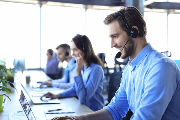 Улыбающийся мужчина-оператор call-центра с наушниками сидит в современном офисе с коллегами на заднем плане, консультируя онлайн.