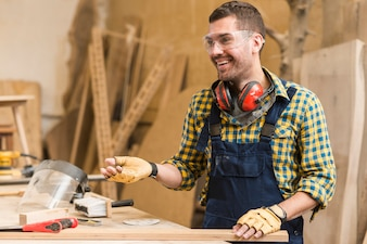 Smiling male carpenter at work in the workshop