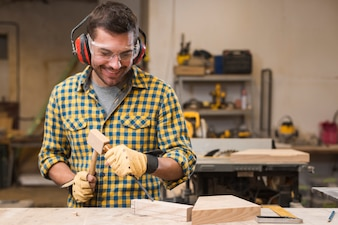 Smiling male carpenter hitting the chisel in the wooden block