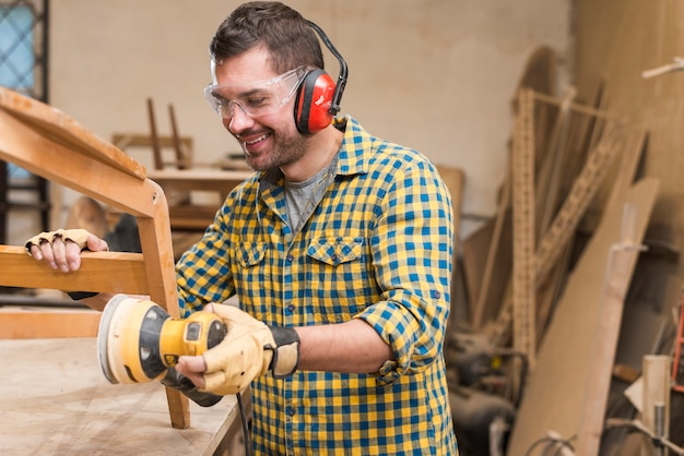 Smiling male carpenter sanding a wood with orbital sander in workbench