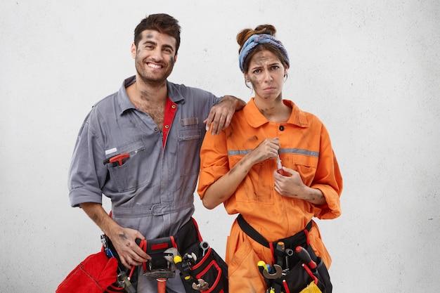 笑顔の男性大工が、動揺して疲れた女性同僚を励ます