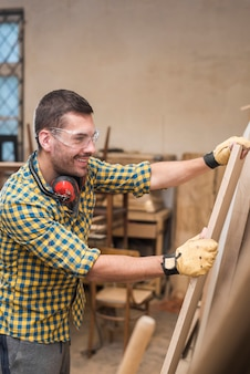 Smiling male carpenter wearing protective gloves holding wooden plank in the workshop