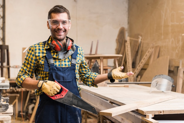 Smiling male carpenter wearing safety glasses holding handsaw gesturing