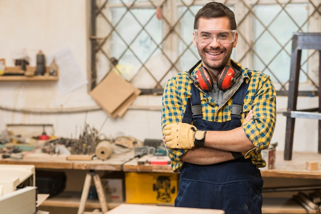 Smiling male carpenter wearing safety glasses standing in front of workbench with his arm crossed