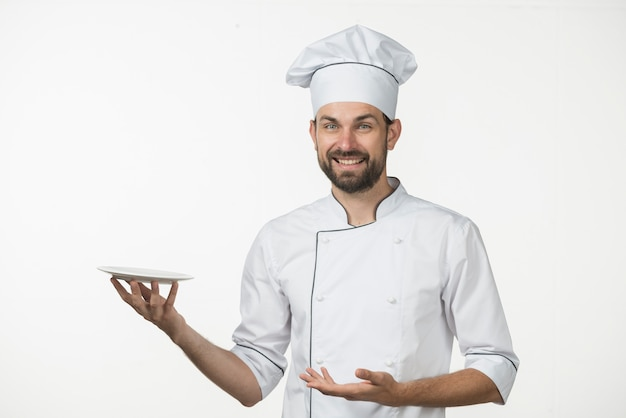 Smiling male chef presenting his dish against white backdrop