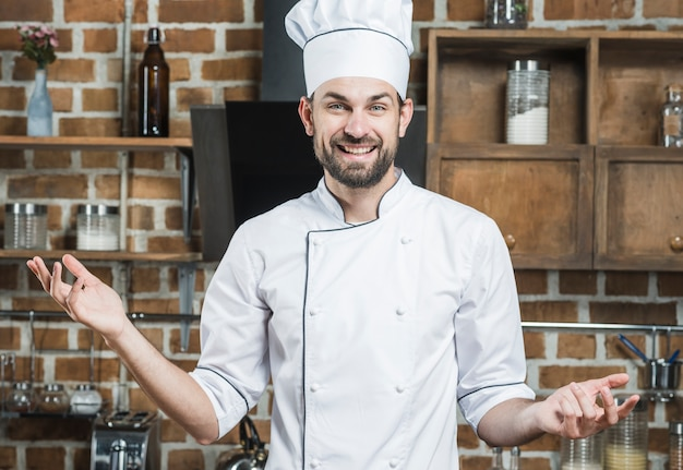 Smiling male chef standing in kitchen shrugging