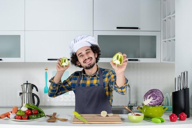 新鮮な野菜で男性シェフを笑顔にし、キッチンツールで調理し、白いキッチンでカットピーマンを保持します