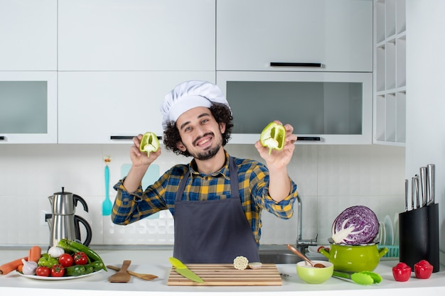 Cuoco maschio sorridente con verdure fresche e cucinare con utensili da cucina e tenere i peperoni verdi tagliati nella cucina bianca