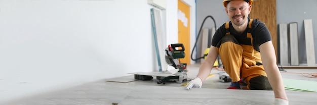 Улыбающийся мужчина-строитель укладывает новое напольное покрытие