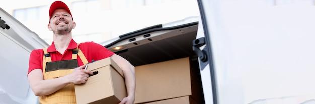 큰 판지 상자를 들고 웃는 남성 택배. 배달 서비스 개념