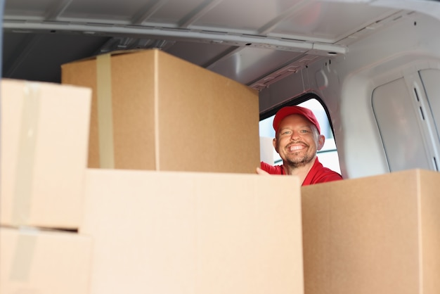 Smiling male courier pulls out cardboard box from car