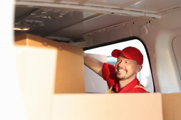 웃는 남성 택배는 차에서 큰 판지 상자를 걸립니다