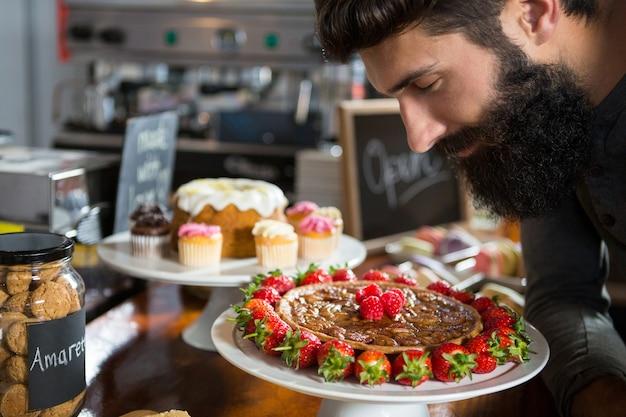 Улыбающийся клиент-мужчина, пахнущий клубничным пирогом за стойкой