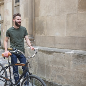 Smiling male cyclist with his bicycle standing beside stone wall