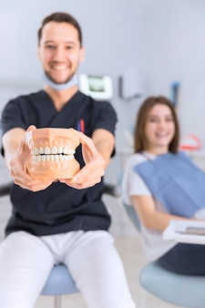 Smiling male dentist showing teeth model sitting in front of female patient