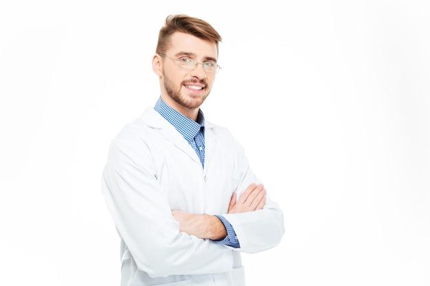 白い背景で隔離の腕を組んで立っている眼鏡で笑顔の男性医師