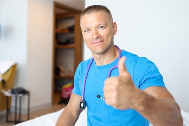 Улыбающийся мужчина-врач делает большие пальцы руки вверх жест концепция качества медицинских услуг