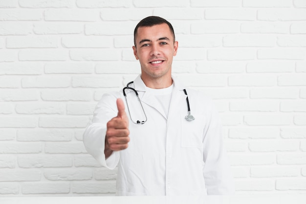 Smiling male doctor posing in front of white bricks wall