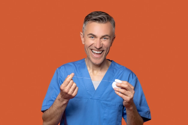 Smiling male doctor showing dental floss