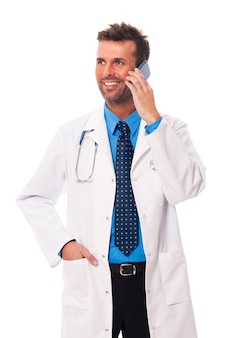 Smiling male doctor talking on mobile phone