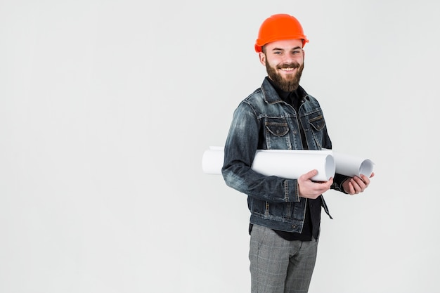 Smiling male engineer holding rolled up blueprint against white background