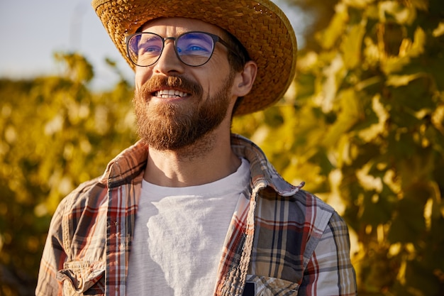 Smiling male entrepreneur in checkered shirt and straw hat looking away with confidence while standing against grape trees in vineyard