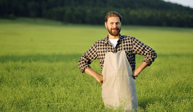 緑の野原に立って笑顔の男性農家
