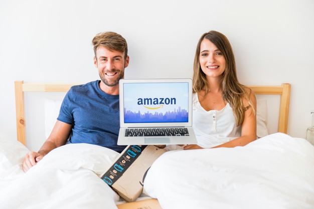 Smiling male and female in bed with laptop