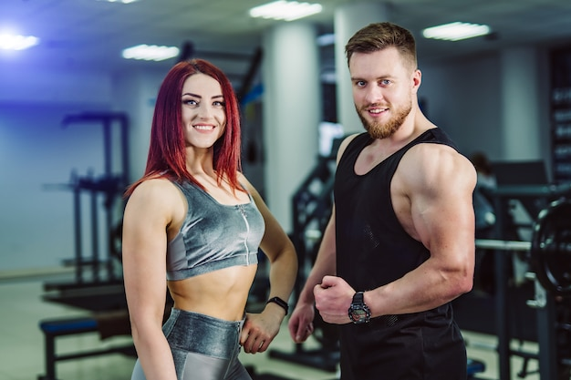 Smiling male and female bodybuilders in sport clothes standing in gym and looking. young couple with muscular bodies posing together in the fitness center.