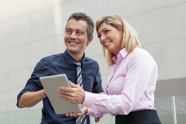 Smiling male and female business people using tablet computer outdoors.