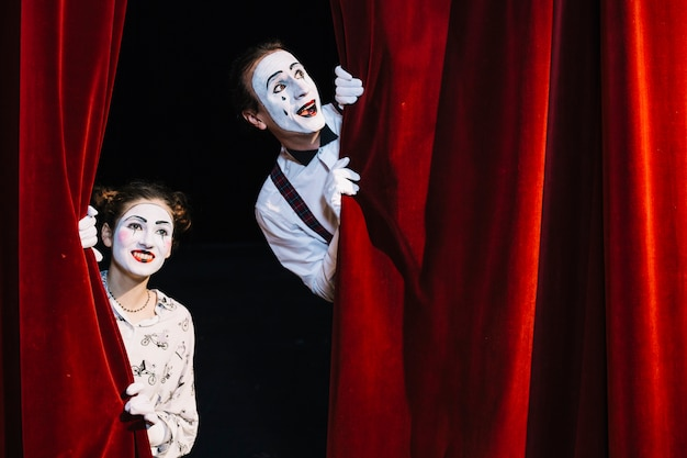 Smiling male and female mime artist peeking from red curtain